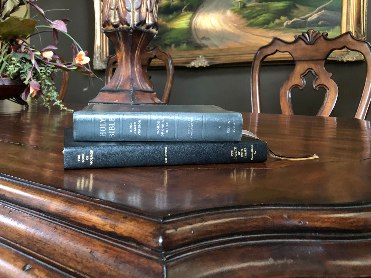 The Holy Bible and the Book of Mormon on a table top.